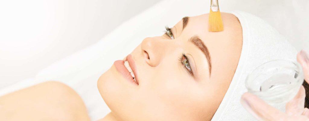 Facial brush peel retinol treatment. Beautiful woman getting a chemical peel procedure.