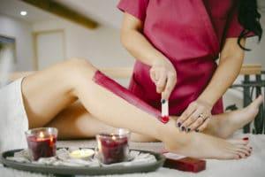 A beautician waxes a woman's leg in a salon - Beautiful female legs - Preparing bodies for the summer